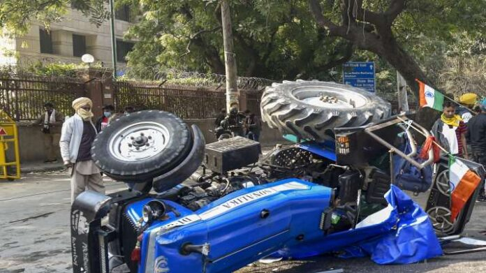 Farmers stand next to an overturned tractor at ITO during