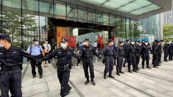 Security personnel forming a human chain as they guard Evergrande's headquarters, where people gathered to demand repayment of loans and financial products in Shenzhen on Monday.